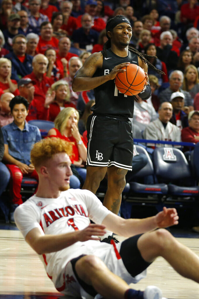 Long Beach State guard Colin Slater, top, reacts after getting called for an offensive foul against Arizona guard Nico Mannion, bottom, in the first half during an NCAA college basketball game, Sunday, Nov. 24, 2019, in Tucson, Ariz. (AP Photo/Rick Scuteri)