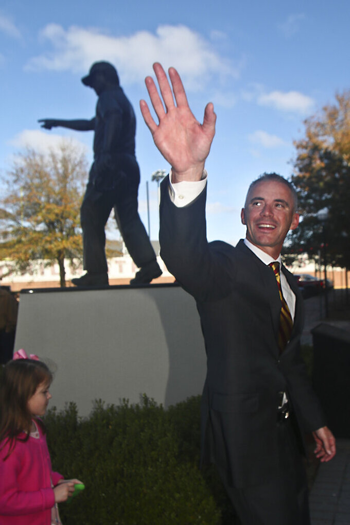 Florida State head football coach Mike Norvell waves as he passes by the Bobby Bowden statue prior to a news conference Sunday, Dec. 8, 2019, in Tallahassee, Fla. Norvell is Florida State's new coach, taking over a Seminoles program that has struggled while he was helping to build Memphis into a Group of Five power. (AP Photo/Phil Sears)
