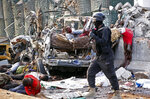 An injured man stuck in the wreckage, center, cries out for help as a member of the security forces walks past amidst the bodies of other dead and injured, at the scene of a bomb blast near the Sahafi hotel in the capital Mogadishu, Somalia, Friday, Nov. 9, 2018. Four car bombs by Islamic extremists exploded outside the hotel, which is located across the street from the police Criminal Investigations Department, killing at least 20 people according to police. (AP Photo/Farah Abdi Warsameh)