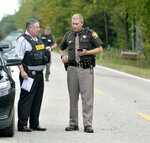 In this Sept. 27, 2017 photo, Isabella County Sheriff Michael Main, right, coordinates efforts in a police manhunt to locate a suspect in Michigan. Main is apologizing for accidentally leaving his gun in a mid-Michigan school gym locker room. Main said in a statement Tuesday, March 13, 2018, that he takes full responsibility and is