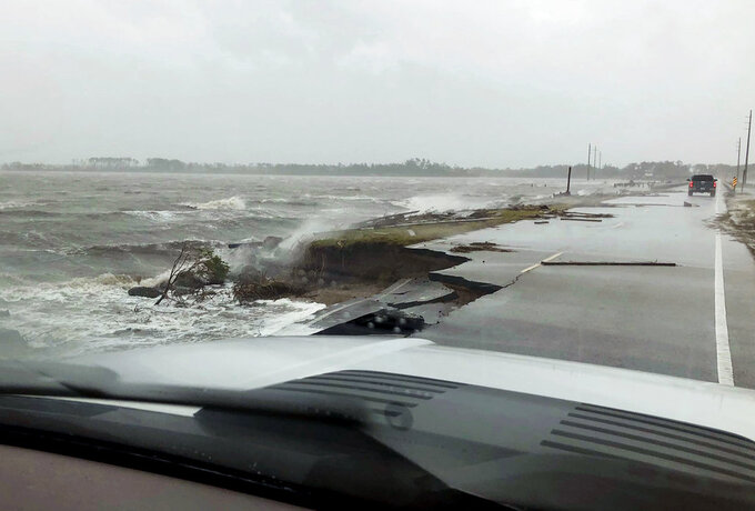 In this photo provided by Jordan Guthrie, wind and water from Hurricane Florence damages the highway leading off Harkers Island, N.C. on Friday, Sept. 14, 2018.  (Jordan Guthrie via AP)