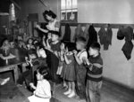 FILE - In this May 1943 file photo, Aiko Sumoge, an assistant teacher, leads a kindergarten class in singing an English folk song at the internment relocation center for Japanese Americans in Tulelake, Calif., during World War II. Beliefs that Hispanics and Asians living in the U.S. won't assimilate or refuse to speak English are based on stereotypes that scholars say are linked to notions of white supremacy. Throughout American history, Hispanics and Asians have been pressured to adopt the customs of the mainstream white population. The pressure came even as some laws forbade them from voting, intermarrying and having access to education and public facilities. (AP Photo, File)