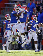 Florida linebacker Ventrell Miller, center left, celebrates after returning an 82-yard interception for a touchdown against Idaho with linebacker Nick Smith (40) during the second half of an NCAA college football game, Saturday, Nov. 17, 2018, in Gainesville, Fla. (AP Photo/John Raoux)