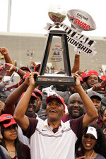 Alabama A&M head coach Connell Maynor hoists the the Southwestern Athletic Conference championship trophy following their NCAA college football game against Arkansas-Pine Bluff, Saturday, May 1, 2021, in Jackson, Miss. Alabama A&M won 40-33. (AP Photo/Rogelio V. Solis)