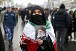 An Iranian woman holds up a portrait of Iranian Supreme Leader Ayatollah Ali Khamenei, as she makes the victory sign during a rally marking the 40th anniversary of the 1979 Islamic Revolution, in Tehran, Iran, Monday, Feb. 11, 2019. Hundreds of thousands of Iranians poured out onto the streets of Tehran and other cities and towns across the country, marking the date 40 years ago that is considered victory day in the country's 1979 Islamic Revolution. (AP Photo/Ebrahim Noroozi)