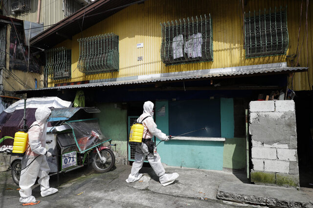 Health workers wearing protective suits disinfect at an area placed under stricter lockdown measures to curb the spread of COVID-19 in Caloocan city, Philippines on Friday, Aug. 14, 2020. The capital and outlying provinces is still under lockdown due to rising COVID-19 cases. (AP Photo/Aaron Favila)