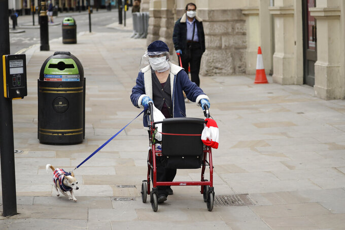 A woman wearing a home made face shield and mask walks a dog near Piccadilly Circus in central London, Sunday, May 3, 2020. The highly contagious COVID-19 coronavirus has impacted on nations around the globe, many imposing self isolation and exercising social distancing when people move from their homes. (AP Photo/Matt Dunham)