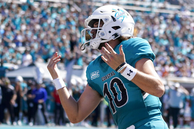 Coastal Carolina quarterback Grayson McCall celebrates after scoring during the first half of an NCAA college football game against Massachusetts on Saturday, Sept. 25, 2021, in Conway, S.C. (AP Photo/Chris Carlson)