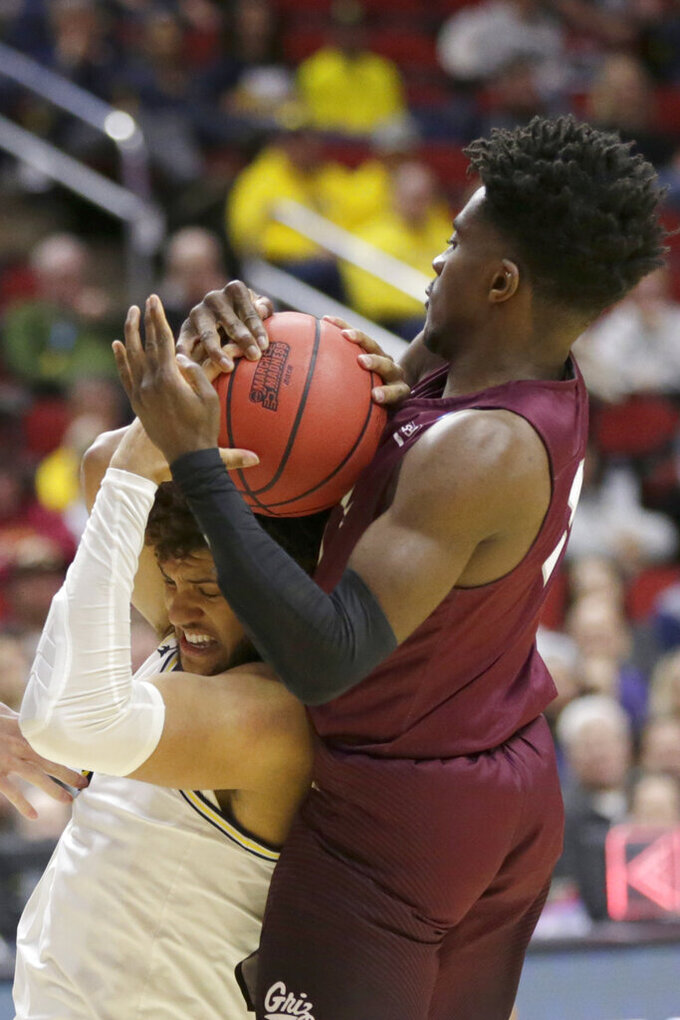 Michigan's Isaiah Livers struggles for the ball against Montana's Michael Oguine, right, during the second half of a first-round game in the NCAA men's college basketball tournament in Des Moines, Iowa, Thursday, March 21, 2019. (AP Photo/Nati Harnik)