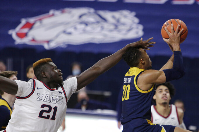 Northern Arizona guard Cameron Shelton (20) shoots and is fouled by Gonzaga center Oumar Ballo (21) during the second half of an NCAA college basketball game in Spokane, Wash., Monday, Dec. 28, 2020. Gonzaga won 88-58. (AP Photo/Young Kwak)