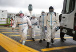 People wearing protective face masks, goggles and Tyvek suits, who said they traveled from Colombia prepare to get into a car rental company shuttle, after arriving at Vancouver International Airport in Richmond, British Columbia., Thursday, Dec. 31, 2020. Beginning January 7, air travelers arriving in Canada will be required to provide proof of a negative COVID-19 test conducted within 72 hours of boarding the plane. (Darryl Dyck/The Canadian Press via AP)