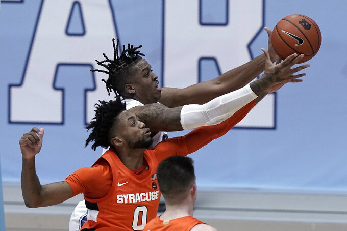 Syracuse forward Alan Griffin (0) and North Carolina forward Armando Bacot chase the ball during the second half of an NCAA college basketball game in Chapel Hill, N.C., Tuesday, Jan. 12, 2021. (AP Photo/Gerry Broome)