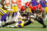 Georgia defensive lineman Malik Herring (10) and defensive back J.R. Reed (20) hit LSU quarterback Joe Burrow (9) during an NCAA college football game for the Southeastern Conference championship Saturday, Dec. 7, 2019, in Atlanta, Ga. (C.B. Schmelter/Chattanooga Times Free Press via AP)