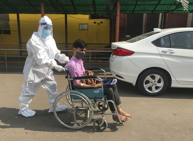 A medical staff in a protective outfit pushes a patient on a wheel chair at a government hospital in Prayagraj, India, Thursday, Nov.5, 2020. With 8.3 million confirmed cases of coronavirus, India is the second worst-hit country behind the United States. (AP Photo/Rajesh Kumar Singh)