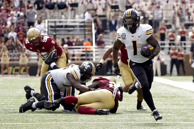 Missouri running back Tyler Badie (1) breaks free from the pile as he rushes for a gain during the first half of an NCAA college football game against Boston College, Saturday, Sept. 25, 2021, in Boston. (AP Photo/Mary Schwalm)