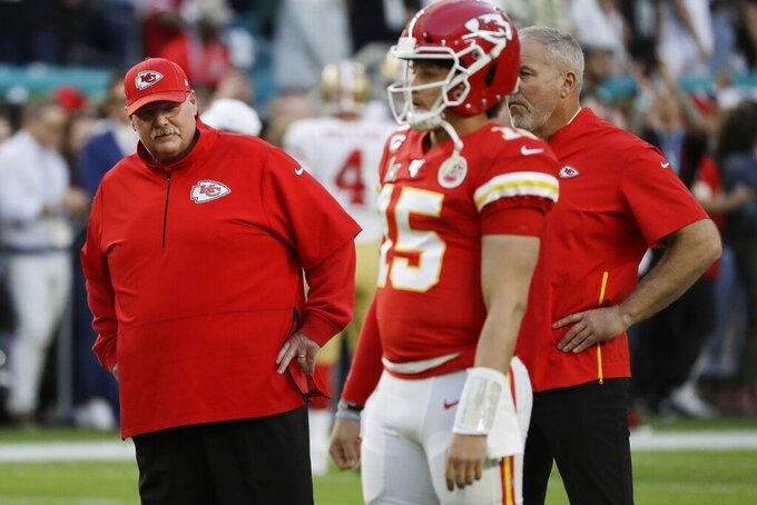 Kansas City Chiefs head coach Andy Reid watches as quarterback Patrick Mahomes (15) warms up before the NFL Super Bowl 54 football game between the San Francisco 49ers and Kansas City Chiefs Sunday, Feb. 2, 2020, in Miami Gardens, Fla. (AP Photo/Seth Wenig)