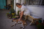 "Tamara Grinberg, 32, pets her dog at her home in San Martin, Buenos Aires province, Argentina, Friday, Jan. 22, 2021. Grinberg who had a clandestine abortion in 2012 said very few people helped her. ""Today there are many more support networks ... and the decision is respected. When I did it, no one respected my decision."