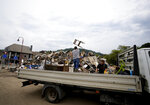 A man throws a chair into a pile of damaged household goods in the town square after flooding in Vaux-sous-Chevremont, Belgium, Saturday, July 24, 2021. Residents were still cleaning up after heavy rainfall hit the country causing flooding in several regions. (AP Photo/Virginia Mayo)