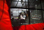 Patients are seen through the window of a tent at a makeshift hospital set up for those who are affected by Sunday's earthquake, in Tanjung, Lombok Island, Indonesia, Friday, Aug. 10, 2018. The magnitude 7.0 quake on Sunday killed hundreds of people and damaged or destroyed thens of thousands of homes. (AP Photo/Fauzy Chaniago)