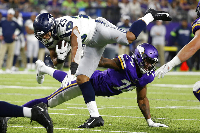 Seattle Seahawks running back Travis Homer (25) is tackled by Minnesota Vikings defensive end Stacy Keely, rear, during the second half of an NFL preseason football game, Sunday, Aug. 18, 2019, in Minneapolis. The Vikings won 25-19. (AP Photo/Bruce Kluckhohn)