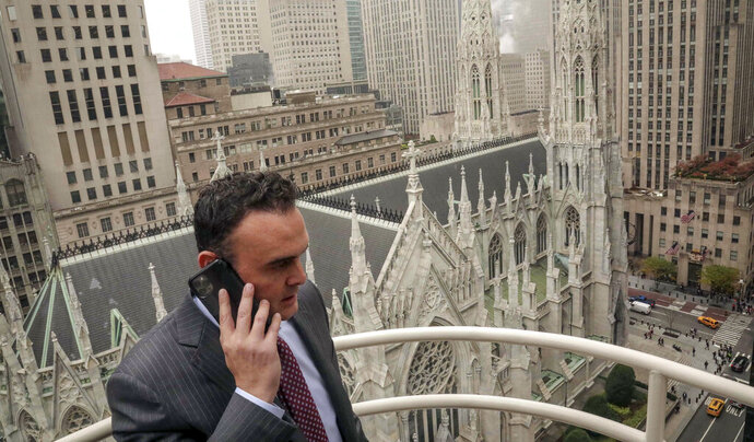 In this Tuesday, Oct. 29, 2019, photo, attorney Adam Slater takes a phone call on a patio outside his high-rise Manhattan office overlooking St. Patrick's Cathedral, in New York. Slater's firm is representing clients accusing the Roman Catholic Church of sexual abuse, a clientele that is rapidly growing after New York state opened its one-year window allowing sex abuse suits with no statute of limitations. (AP Photo/Bebeto Matthews)