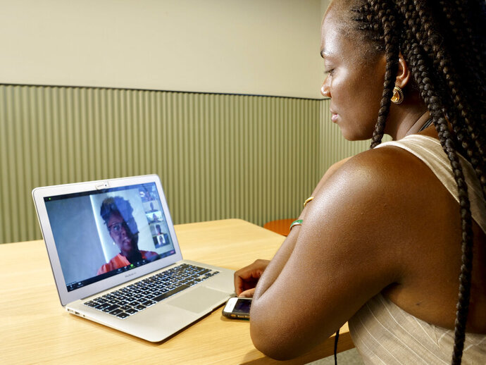 Kave Bulambo, founder of Black in Tech Berlin speaks with other members of the tech group via video call in the conference room of the public co-working space where she often works in Berlin, Germany, Aug. 21, 2020. (AP Photo/Jona Kallgren)