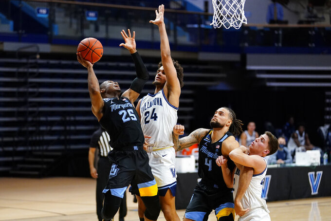 Marquette's Koby McEwen (25) goes up for a shot against Villanova's Jeremiah Robinson-Earl (24) during the second half of an NCAA college basketball game, Wednesday, Feb. 10, 2021, in Villanova, Pa. (AP Photo/Matt Slocum)