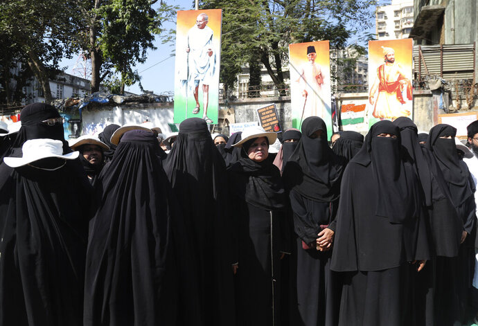 Indian Muslim women observe two minutes of silence to mark the death anniversary of India's independence leader Mahatma Gandhi during a protest against a new citizenship law that opponents say threatens India's secular identity, in Mumbai, India, Thursday, Jan. 30, 2020. The new citizenship law and a proposed National Register of Citizens have brought thousands of protesters out in the streets in many cities and towns since Parliament approved the measure on Dec. 11. (AP Photo/Rafiq Maqbool)