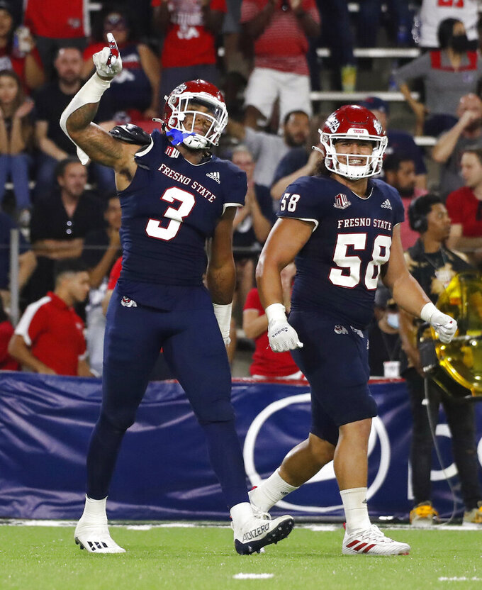 Fresno State defensive tackle Arron Mosby, left, and linebacker Tyson Maeva celebrate a sack against UNLV during the second half of an NCAA college football game in Fresno, Calif., Friday, Sept. 24, 2021. (AP Photo/Gary Kazanjian)