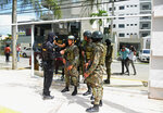 Narcotics police and soldiers stand outside a building, behind, related to César Emilio Peralta, also known as