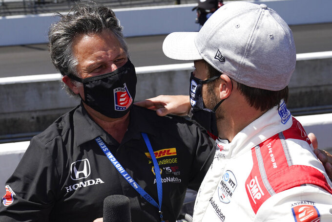 Marco Andretti is congratulated by Michael Andretti after Marco won the pole for the Indianapolis 500 auto race at Indianapolis Motor Speedway, Sunday, Aug. 16, 2020, in Indianapolis. (AP Photo/Darron Cummings)