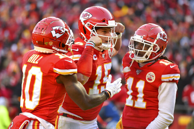 Kansas City Chiefs' Patrick Mahomes (15) celebrates with Tyreek Hill (10) and Demarcus Robinson after running for a touchdown during the first half of the NFL AFC Championship football game against the Tennessee Titans Sunday, Jan. 19, 2020, in Kansas City, MO. (AP Photo/Ed Zurga)