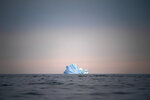 FILE - In this Aug. 15, 2019, file photo, a large Iceberg floats away as the sun sets near Kulusuk, Greenland. As warmer temperatures cause the ice to retreat the Arctic region is taking on new geopolitical and economic importance, and not just the United States hopes to stake a claim, with Russia, China and others all wanting in. (AP Photo/Felipe Dana, File)