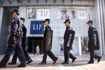 Chinese police patrol in formation past a store from American clothing retailer Gap at an outdoor shopping area in Beijing, Tuesday, Sept. 25, 2018. A Chinese trade envoy said Tuesday that talks with Washington are impossible while the United States