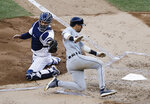 Detroit Tigers' Nicholas Castellanos, right, runs past New York Yankees catcher Gary Sanchez, left, to score on a sacrifice fly ball fourth inning of a baseball game Wednesday, April 3, 2019, in New York. (AP Photo/Frank Franklin II)