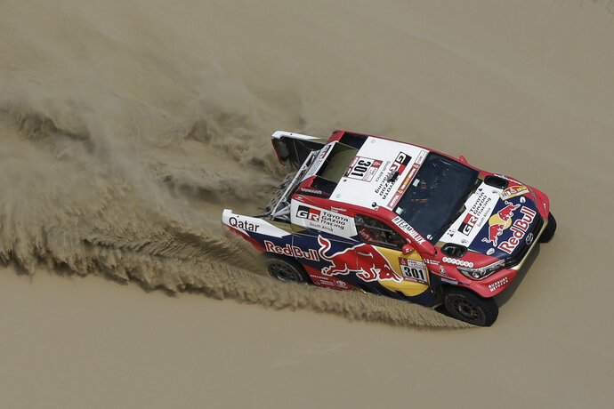 Driver Nasser Al-Attiyah, of Qatar, and co-driver Matthieu Baumel, of France, race their Toyota during the third stage of the 2018 Dakar Rally between Pisco and San Juan de Marcona, Peru, Monday, Jan. 8, 2018. (AP Photo/Ricardo Mazalan)
