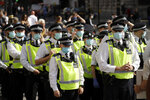 Police officers wearing face masks stand next to a