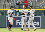 From left, San Francisco Giants left fielder Mike Tauchman, center fielder Steven Duggar and right fielder Austin Slater celebrate after the seventh inning of game one of a baseball doubleheader against the Colorado Rockies Tuesday, May 4, 2021, in Denver. The Giants won the opening game of the twinbill by a score of 12-4. (AP Photo/David Zalubowski)
