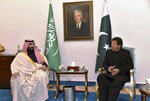 In this photo released by the Press Information Department, visiting Saudi Arabia's Crown Prince Mohammed bin Salman, left, listens to Pakistani Prime Minister Imran Khan during a meeting in Islamabad, Pakistan, Sunday, Feb. 17, 2019.  Saudi Arabia's powerful Crown Prince Mohammed bin Salman began his four-day regional visit on Sunday, arriving in Pakistan where he is expected to sign agreements worth billions of dollars to help the Islamic nation overcome its financial crisis. (Press Information Department, via AP)
