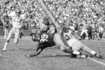 FILE - In this Nov. 6, 1971, file photo, Southern California fullback Sam Cunningham (39) is  brought down by Washington State's Eric Johnson after picking up 16 yards at the Los Angeles Coliseum in Los Angeles. Cunningham, an All-American fullback at Southern California whose performance against Alabama was credited for helping integrate football in the Deep South before he went on to a record-setting career with the New England Patriots, died Tuesday, Sept. 7, 2021, at his home in Inglewood, Calif., according to USC. He was 71. (AP Photo/David F. Smith, File)