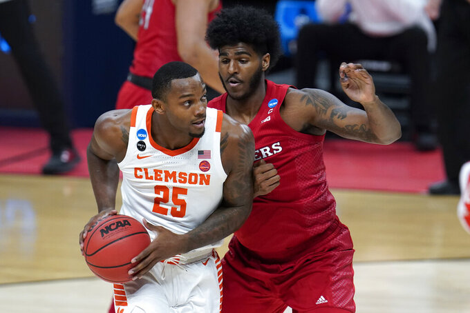 Clemson forward Aamir Simms (25) drives on Rutgers center Myles Johnson during the first half of a men's college basketball game in the first round of the NCAA tournament at Bankers Life Fieldhouse in Indianapolis, Friday, March 19, 2021. (AP Photo/Paul Sancya)