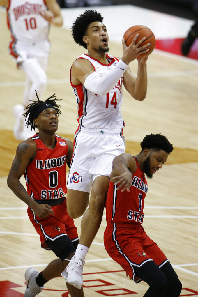 Ohio State's Justice Sueing, center, jumps between Illinois State's DJ Horne, left, and Dedric Boyd to shoot during the first half of an NCAA college basketball game Wednesday, Nov. 25, 2020, in Columbus, Ohio. (AP Photo/Jay LaPrete)