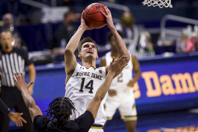 Notre Dame's Nate Laszewski (14) goes up for a shot over Miami's Isaiah Wong during the second half of an NCAA college basketball game Sunday, Feb. 14, 2021, in South Bend, Ind. Notre Dame won 71-61. (AP Photo/Robert Franklin)