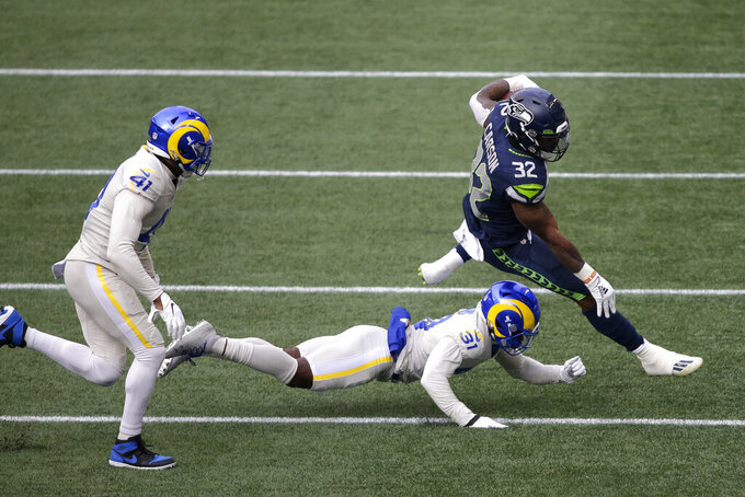Seattle Seahawks running back Chris Carson (32) leaps to try and avoid a tackle from Los Angeles Rams cornerback Darious Williams (31) as inside linebacker Kenny Young (41) closes in during the first half of an NFL football game, Sunday, Dec. 27, 2020, in Seattle. (AP Photo/Scott Eklund)