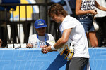 Los Angeles Chargers quarterback Justin Herbert, right, signs an autograph for a fan after practice at the NFL football team's training camp in Costa Mesa, Calif., Wednesday, July 28, 2021. (AP Photo/Alex Gallardo)
