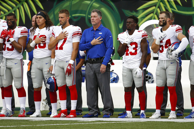 New York Giants coach Pat Shurmur, center, and players stand for the national anthem before the team's NFL preseason football game against the Cincinnati Bengals, Thursday, Aug. 22, 2019, in Cincinnati. (AP Photo/Frank Victores)