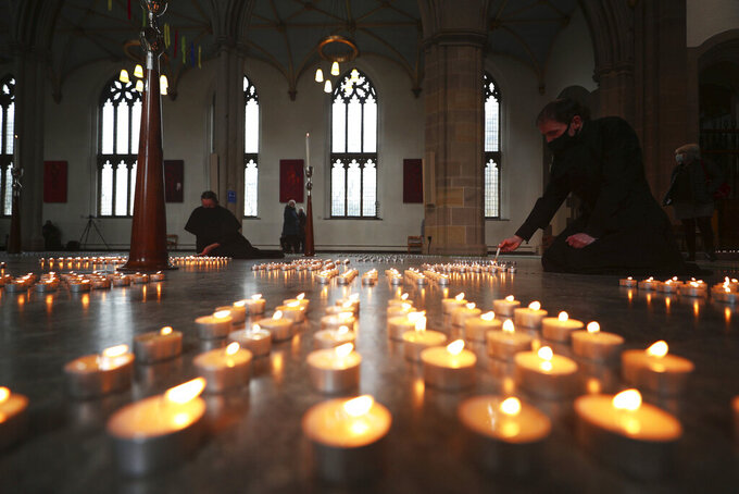 Candles are lit during the National Day of Reflection at Blackburn Cathedral, on the anniversary of the first national lockdown to prevent the spread of coronavirus, in Blackburn, England, Tuesday March 23, 2021.  The U.K. has a lot to reflect on a year after British Prime Minister Boris Johnson first announced that the country would go into lockdown to slow the fast-spreading coronavirus. A national day of reflection taking place on Tuesday will remember more than 126,000 people who died after contracting the virus. (Peter Byrne/PA via AP)