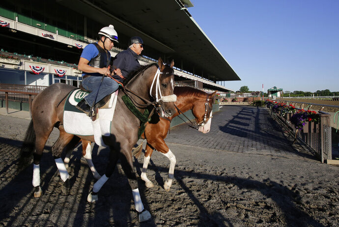 "FILE - In this June 4, 2013, file photo, Preakness winner Oxbow, left, enters the track for a light workout at Belmont Park in Elmont, N.Y. Trainer D. Wayne Lukas is at rear. The order of the Triple Crown races could be different this year. ""If you go from a mile-and-a-half and start dropping back, it's going to change a lot,"" said Lukas, winner of 14 Triple Crown races. ""It'll change how you train, it'll change the type of horse that will end up in the Derby. It'll be a very, very significant change."" (AP Photo/Mark Lennihan, File)"
