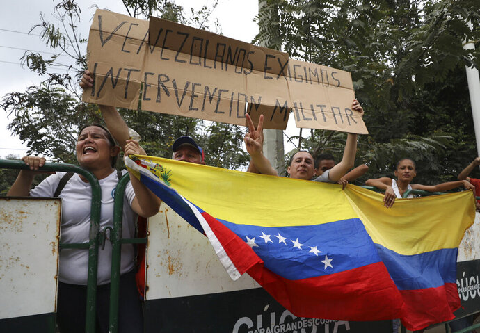 People hold a Venezuelan flag and the Spanish message: