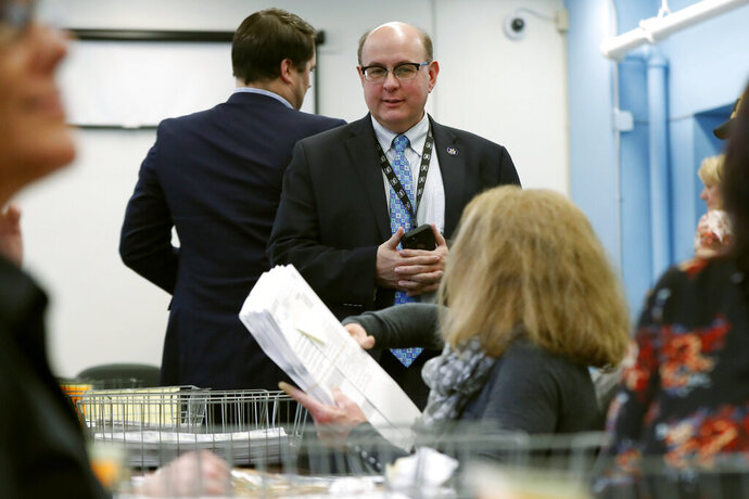 FILE - In this Dec. 6, 2018, file photo, Maine Secretary of State Matt Dunlap oversees the recounting of ballots in the state's 2nd Congressional District, in Augusta, Maine. Dunlap is wrapping up his tenure after a frenetic four-year span in which he ushered in rules for voter-approved ranked-choice voting. Several Democrats hope to replace him when the new legislature convenes in December 2020. (AP Photo/Robert F. Bukaty, File)